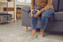 Person Sitting On Sofa At Home After Hurting Knee Joint In Domestic Accident. Young Woman, Suffering From Arthritis, Osteoarthritis Pain Or Rheumatic Disorder, Massaging Painful Knee Cap With Hands