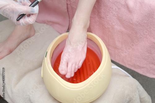 Obraz na płótnie woman foot treatment in paraffin bath at the spa.