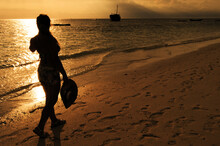Walking Along The Beach At Sunset