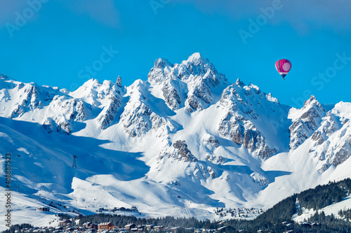 Leinwand Poster Vivid red colorful hot air balloon over Courchevel valley in French Alps