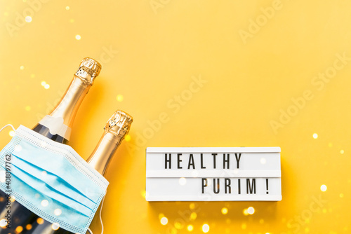 Healthy Purim written in lightbox, two champagne bottles, and medical mask on a yellow background Wallpaper Mural
