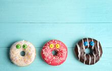 Delicious Donuts Decorated As Monsters On Light Blue Wooden Table, Flat Lay With Space For Text. Halloween Treat