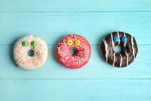 Delicious Donuts Decorated As Monsters On Light Blue Wooden Table, Flat Lay. Halloween Treat