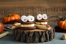 Delicious Desserts Decorated As Monsters On Blue Wooden Table. Halloween Treat