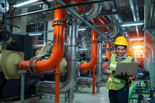 Industrial Plant In Factory, Women Worker Using  Laptop On Chiller Water Cool In Plant Room Background.