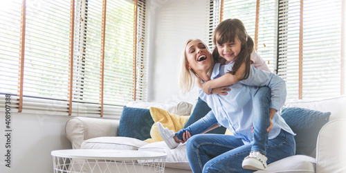 Foto Happy Beautiful Mother carrying or piggyback her little daughter laughing playin