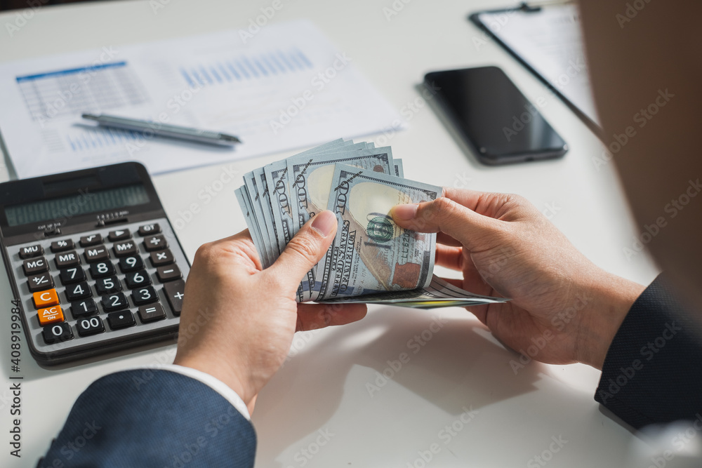 Fototapeta Closeup hands businessman banker counting money banknote dollars, bank financial and investment concept