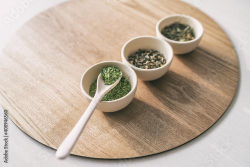 Fototapeta Green tea tasting, loose leaf dried leaves cups chinese teas rustic natural background. Spoon and teacups. obraz
