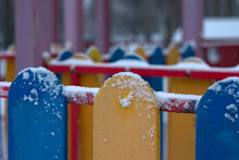 Snow On The Colorful Fence Of The Playground