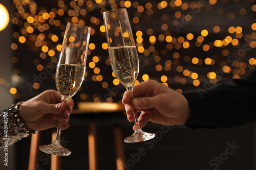 People clinking glasses of champagne indoors, closeup © New Africa