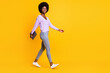 Full body profile photo of pretty dark skin person walking arm hold laptop isolated on yellow color background