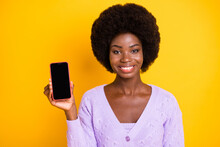 Photo Of Pretty Cheerful Dark Skin Person Hold Show Phone Display Empty Space Isolated On Yellow Color Background