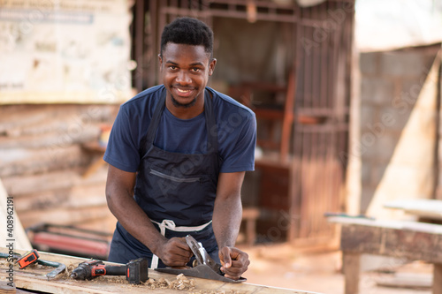 Obraz young african carpenter smiling while working - fototapety do salonu