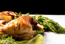 Rabbit Meat Baked With Vegetables And Herbs On A Plate On A Black White Background.
