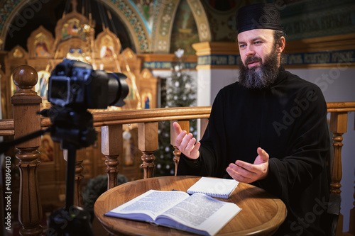 Obraz na plátne . Priest online. An Orthodox priest is recording a video for his blog. Preaching