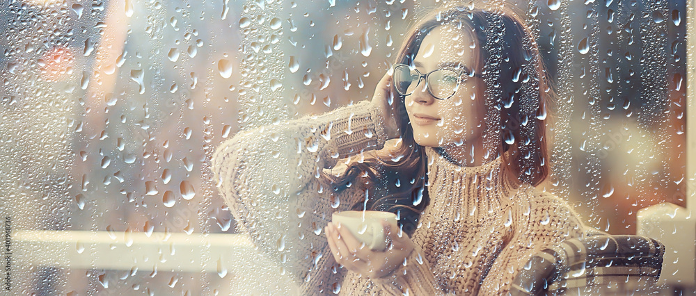 Fototapeta autumn coffee on a rainy day, girl behind a glass with a cup of hot coffee