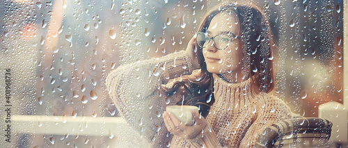 Fototapeta autumn coffee on a rainy day, girl behind a glass with a cup of hot coffee obraz