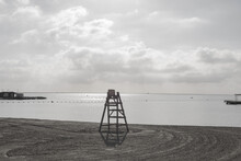 A Sandy Beach Near The Coast With A Baywatch Tower Made Out Of Wood Near The Water Or River Or Lake Seen On A Cloudy Spring Day Out