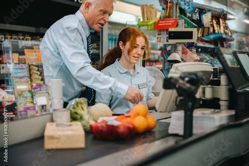 Obraz na płótnie Manager teaching new employee at supermarket