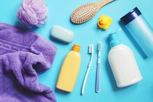Flat Lay Composition Bath Products On A Blue Background. Purple Towel, Shampoo Bottle, Sponge, Soap Bar, Shower Gel, Hair Balm, Comb, Toothbrushes And Rubber Duck. Toiletries Set