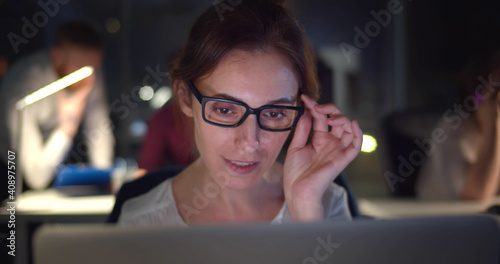 Businesswoman working with colleagues in dark office.
