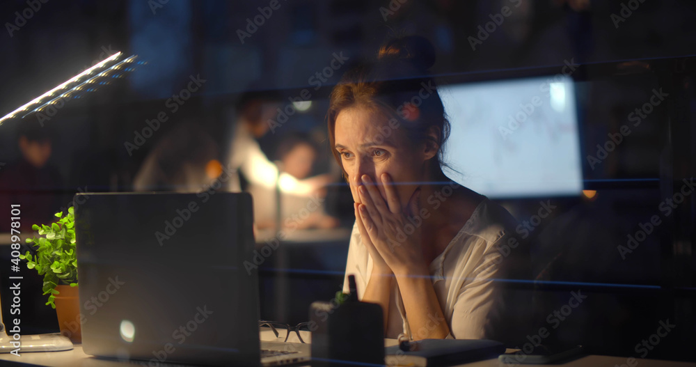 Fototapeta Stressed businesswoman with computer working at night office