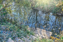Rustic Wooden Steps To Calm Narrow River With Green Grass Covered With Rime On Banks At Countryside In Early Autumn Morning