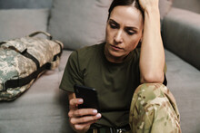 Serious Soldier Woman Using Mobile Phone While Sitting On Floor