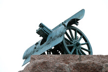 Antique Cannon On A Stone Pedestal Against The Sky