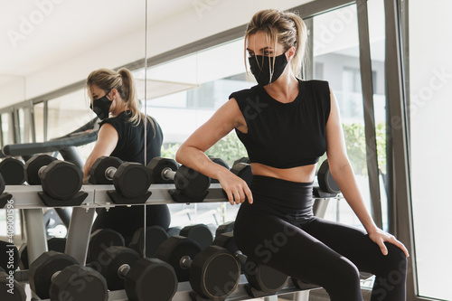 Obraz Young athletic woman wearing a prevention face mask during her fitness workout. - fototapety do salonu