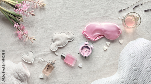 Healthy night sleep concept. Off white, ivory textile flat lay. Pink hyacinth flower.Sleep mask, tea, glass,. Soft toys, clouds and heart. Fluffy bottle warmer, orthopedic pillow. © tilialucida