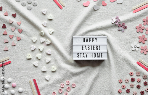 Happy Easter Stay Home text on lightbox. Flat lay with light box on ivory, off white textile. Hearts, candy, buttons, small decor arranged on cotton tablecloth. © tilialucida