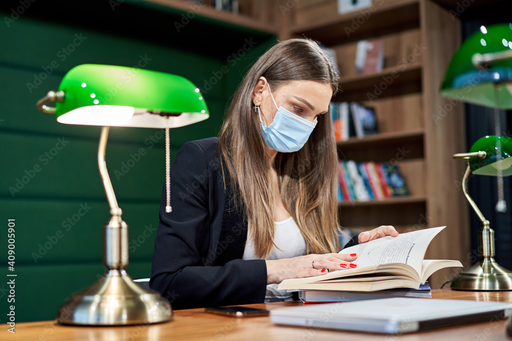 Fototapeta Woman in protective mask reading a book in library