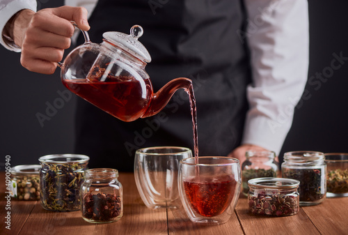 Canvas Print Tea master pouring red tea into glass cups
