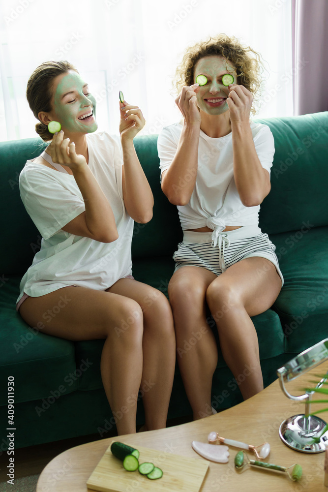 Fototapeta Two beautiful girls with applied facial masks during spa day