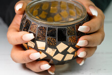 Female Finger Nails With Hands Holding On To Golden Metallic Bowl