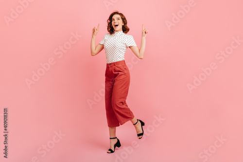 Obraz Gorgeous girl in black shoes dancing in studio. Glad curly lady pointing with fingers up. - fototapety do salonu