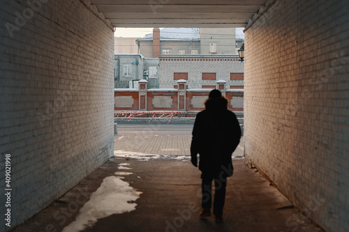 Fotografering A silhouette of a man in black outfit walking in alleyway