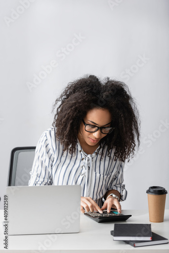 Obraz african american freelancer in glasses using calculator while counting near laptop and paper cup on desk - fototapety do salonu