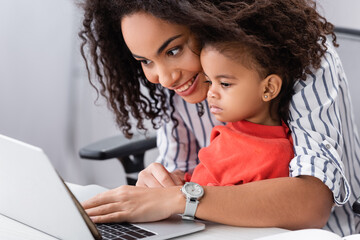 happy african american mother looking at laptop with toddler daughter