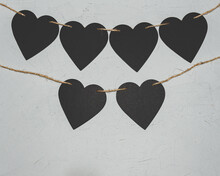 Black Paper Hearts On Grey Background. Valentine's Day Loft Concept.