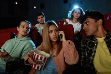 Attractive Young Woman Talking On The Phone, Annoying Audience While Watching Movie With Friends At The Cinema