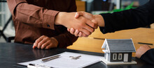 Real Estate Agents Shaking Hands To Congratulate Buyers After Giving Buyers A Purchase Contract, A Contract Idea. Trading Houses And Real Estate