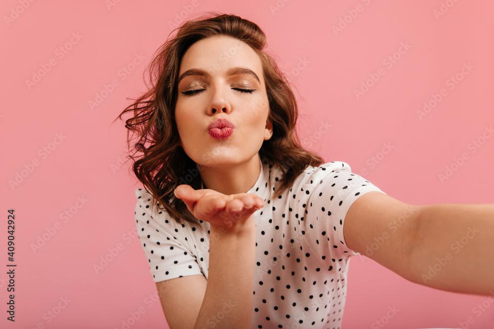 Fototapeta Pleasant girl sending air kiss and taking selfie. Amazing woman expressing love on pink background.