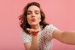 Pleasant girl sending air kiss and taking selfie. Amazing woman expressing love on pink background.
