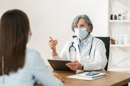 Fotografía Senior mature female doctor in a lab coat and a face mask sitting at the desk,ho