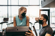 Young fit and attractive woman at body workout in modern gym together with her personal fitness instructor or coach. They keeping distance and wearing protective face masks. Coronavirus sport theme.