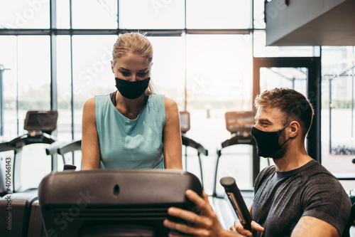 Obraz Young fit and attractive woman at body workout in modern gym together with her personal fitness instructor or coach. They keeping distance and wearing protective face masks. Coronavirus sport theme. - fototapety do salonu