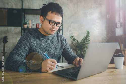 Obraz Asian man working with computer laptop. concept work form home, online education, e-learning, stay at home. freelance life style, new normal life style, covid-19 pandemic, after coronavirus outbreak. - fototapety do salonu