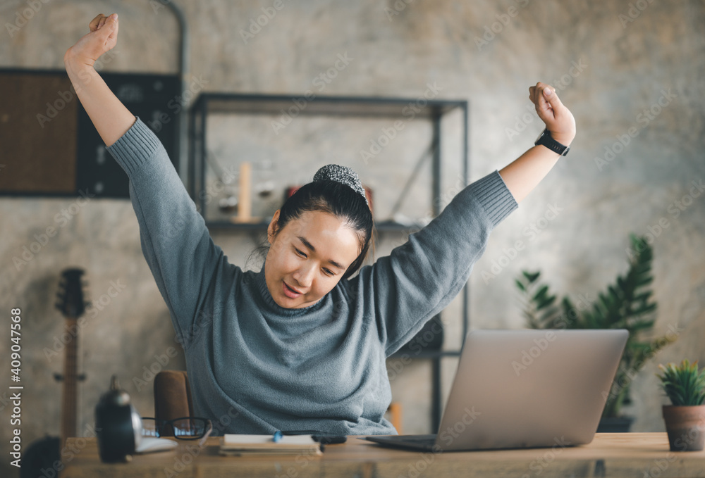 Fototapeta Young Asian Business woman stretching herself and exercise for relaxation while working at home office. work from home concept. new normal life style, covid-19 pandemic, after coronavirus outbreak.
